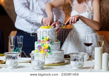 Groom In Suit And Bride In White Dress Cut Beautiful Multi Level Wedding Cake, Decorated With Cream