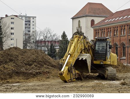 Building Site - An Excavator Stands On The Ground