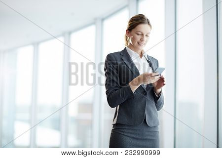 Well-dressed agent with smartphone reading message and texting inside modern business center