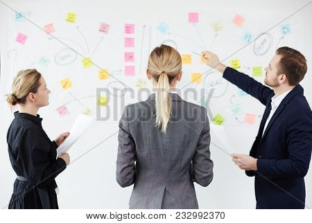 Two businesswomen looking at whiteboard while their colleague explaining scheme of teamwork