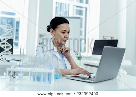 Working On Research. Beautiful Serious Dark-haired Researcher Wearing A Uniform While Working On Her