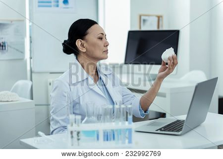 Important Research. Attractive Concentrated Dark-haired Researcher Wearing A Uniform While Holding A