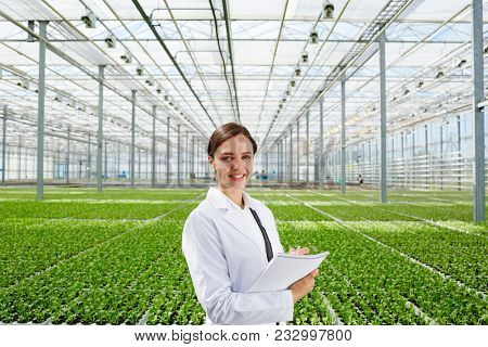 Young successful biologist in whitecoat on background of large green plantation in glasshouse