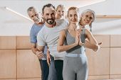 cheerful senior people smiling at camera while instructor showing namaste sign poster