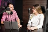 Portrait of male radio presenter interviewing a woman guest in a radio studio for a podcast poster