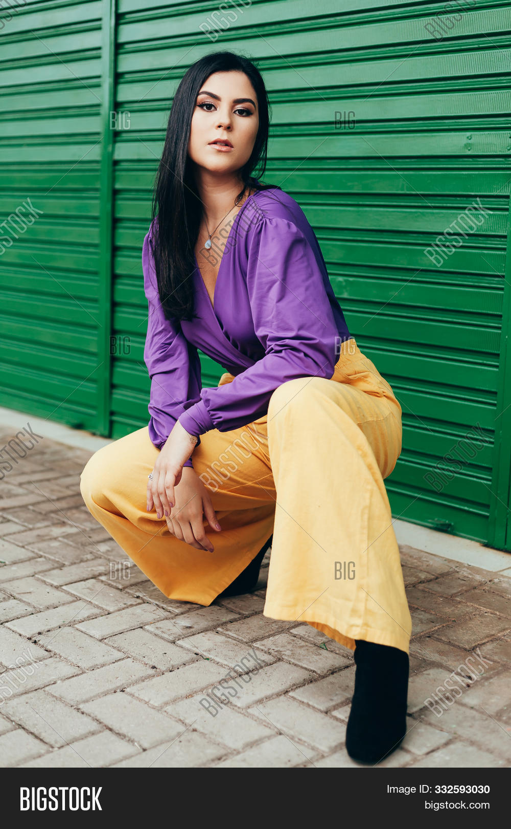 Outdoor Fashion Portrait Of Woman Wearing Clothes In Complementary Yellow And Purple Colors