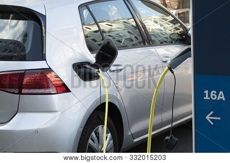 Charging The Electric Car Silver Color. Charging Station For Electric Car. Power Supply For Electric