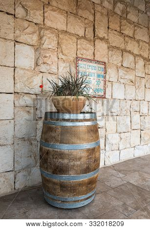Rosh Haayin, Israel, October 31, 2019 : Wine Barrel And Flower Pot Near The Entrance To The Psagot W