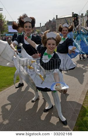 Performers dresses as waitresses serve cakes on Exeter Cathedral Green