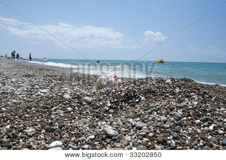 Young Boy Covered In Pebbles On A Holiday Beach