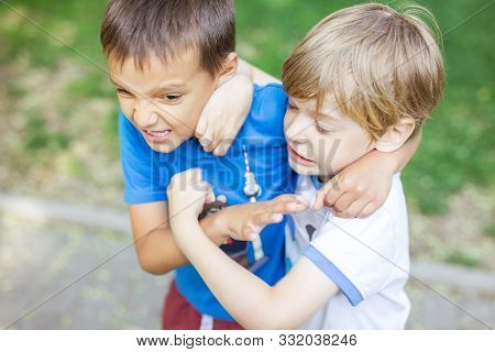 Two Boys Fighting Outdoors. Friends Wrestling In Summer Park. Siblings Rivalry.