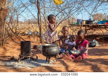 african children in a village near Kalahari desert, the sister feeding her brother in the outdoors kitchen