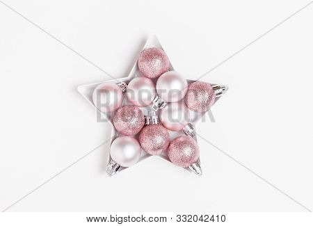 Christmas Composition. Pink And Silver Christmas Balls Laid Out In The Shape Of A Star On White Back