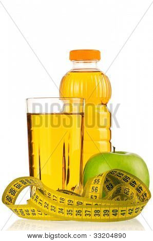 Apple juice in plastic bottle and glass with a measure tape isolated on white background