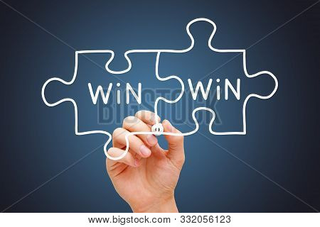 Hand Drawing Win-win Jigsaw Puzzle Business Concept With White Marker On Transparent Wipe Board.
