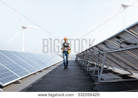 View On The Rooftop Solar Power Plant With Mann Walking And Examining Photovoltaic Panels. Concept O
