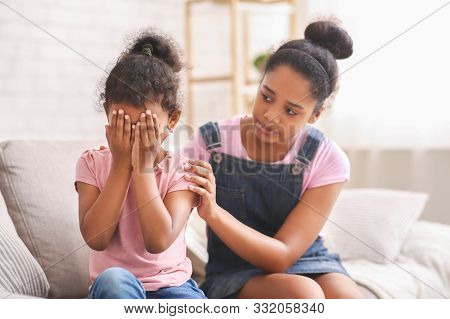 Siblings Relationships And Support Concept. African Teen Girl Embracing Crying Baby Sister, Apologiz