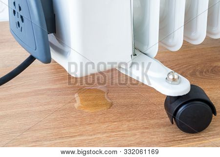Oil Drips Onto The Floor From A Damaged Oil Heater. Malfunction Of The Electric Home Radiator And Re