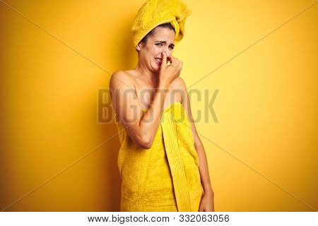 Beautiful woman wearing shower towel on body and head over yellow isolated background smelling something stinky and disgusting, intolerable smell, holding breath with fingers on nose. Bad smell