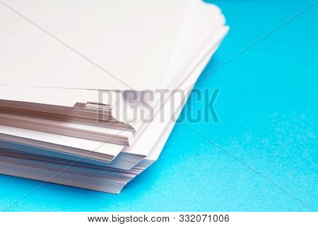 A Stack Of Clean White Paper On A Table On A Blue Background. Blank Pages Ready For Printing And Wri