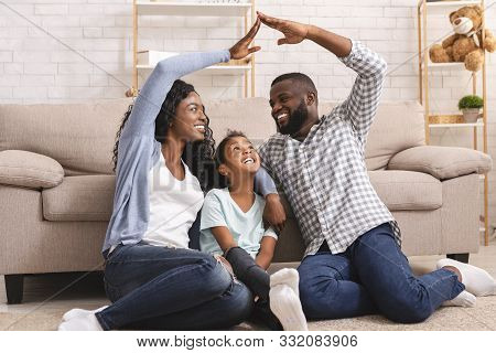 Family Care And Protection Concept. Black Parents Making Symbolic Roof Of Hands Above Their Little D