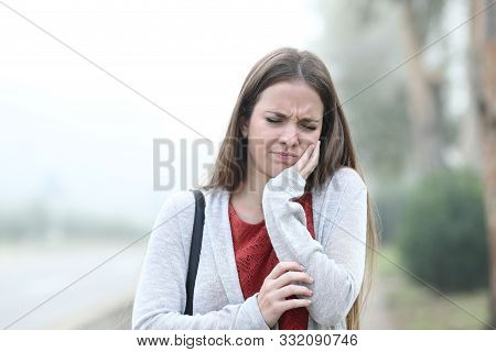 Front View Portrait Of An Woman Suffering Tooth Ache A Foggy Day