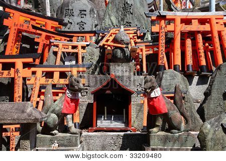 Fushimi Inari Taisha shrine in Kyoto prefecture of Japan. Famous shinto shrine. Statues of fox messengers (kitsune). poster