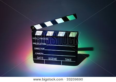 Black cinema clapperboard, which is multicolored highlighted