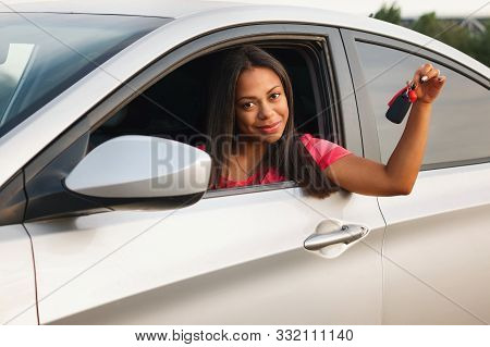 Lovely African American Woman Posing While Sitting In A Car Salon With Keys. Woman Afro American Dri