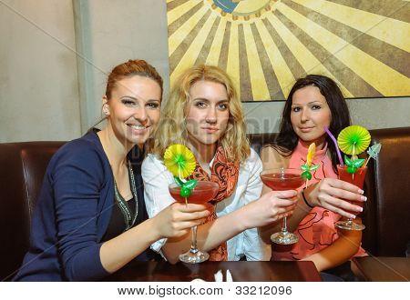 Three girls drinking cocktails