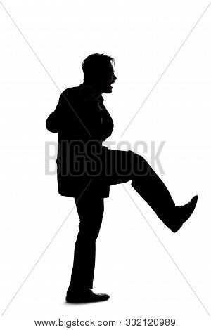 Silhouette Of A Backlit Model Posing As A Businessman On A White Background.  He Is Kicking Out Of F