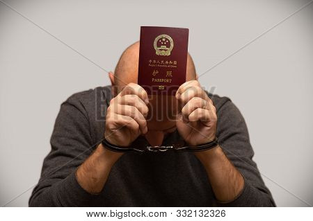 The Problem Of Illegal Immigration Of Refugees From China, An Immigrant From China In Handcuffs.