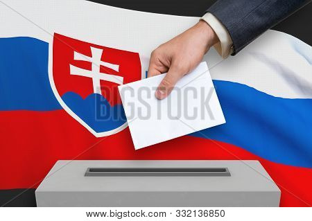 Election In Slovakia - Voting At The Ballot Box. The Hand Of Man Is Putting His Vote In The Ballot B