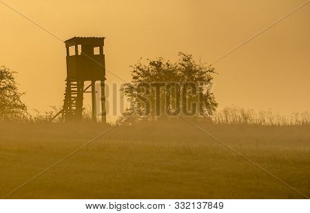 Hunting Tower During Sunrise On A Beautiful Foggy Morning.