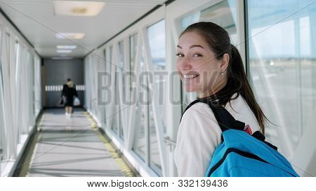 Happy Young Woman With Backpack Is Going On Telescopic Gangway To The Airplane. She Turns Around, Lo