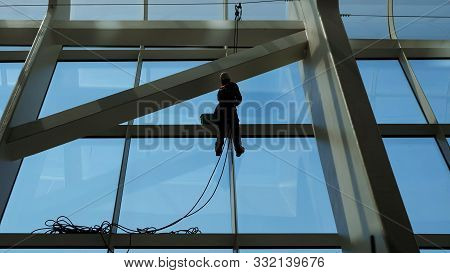 Faceless Worker Man Is Washing Windows With Scraper On A Highrise Modern Building Hanging The Rope.