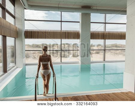 Young girl relaxing in luxury spa hotel with indoor swimming pool