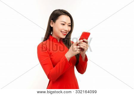 An Asian Cute Woman In Vietnamese Traditional Dress Is Using Mobile Phone For Chatting