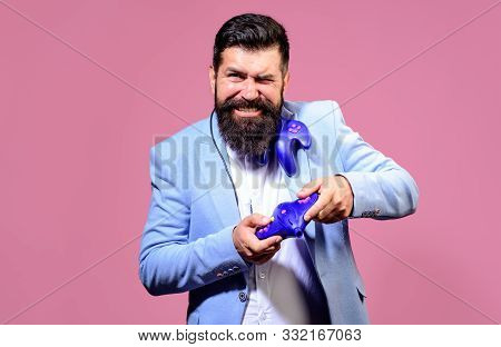 poster of Businessman with joystick. Guy playing on console. Smiling bearded man using video-game controller. Handsome man with game controller playing video games. Gamer man with gamepad playing in video game