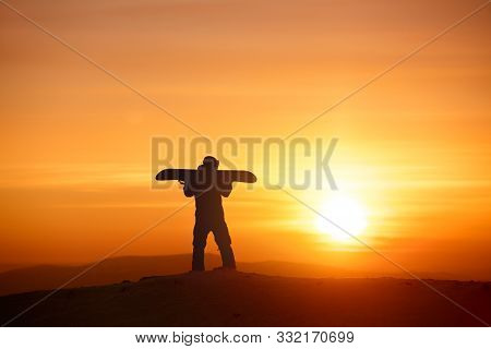 Snowboarder Silhouette Stands With Snowboard Against Sunset Light And Sun. Ski Resort Concept
