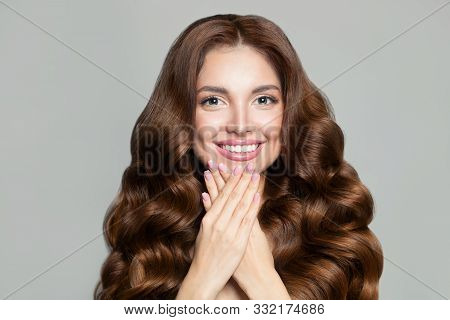 Beautiful Woman With Long Healthy Brown Curly Hair. Gorgeous Model With Natural Makeup And Perfect H