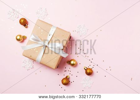 Christmas Greeting Card Composition. Craft Paper Gift With White Ribbon On Pink Background With Chri