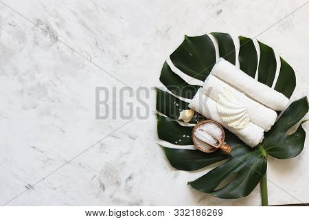 Spa Massage Products With Monstera Leaves On Marble Background. Top View, Copy Space
