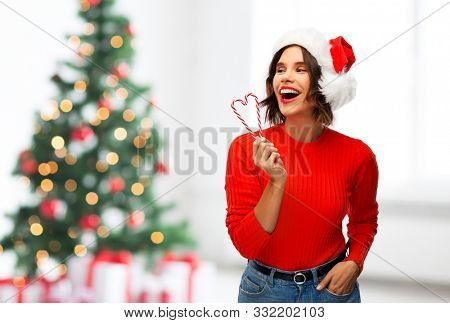 winter holidays and people concept - happy smiling young woman in santa helper hat with candy canes over christmas tree lights background
