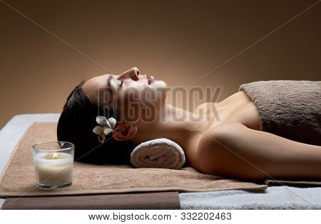 wellness, beauty and relaxation concept - young woman lying at spa or massage parlor with burning aromatic candle