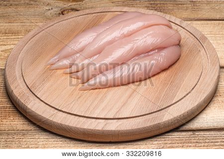 Raw, Fresh Small Inner Chicken Fillet. Small Inner Chicken Fillet On A Wooden Cutting Board.