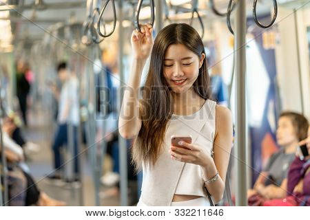 Young Asian Woman Passenger Using Social Network Via Smart Mobile Phone In Subway Train When Traveli