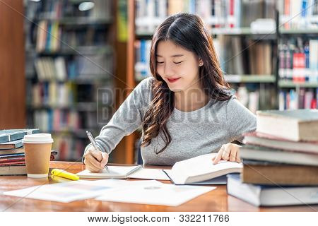 Asian Young Student In Casual Suit Reading And Doing Homework In Library Of University Or Colleage W