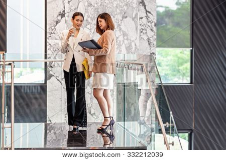 Two asian businesswomen walking and talking during coffee break in modern office or coworking space, coffee break, relaxing and talking after working time, business and people partnership concept poster
