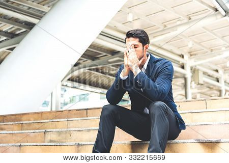 Portrait Of Young, Depressed Man In Pain And Suffering From Work. Businessman Palms  Cover His Face